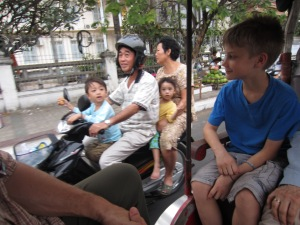 Braxton engaging in cross-cultural exchange from back of tuk tuk, Phnom Penh, Cambodia