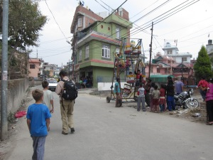 Strolling home past hand-cranked ferris wheel, Boudha, Nepal