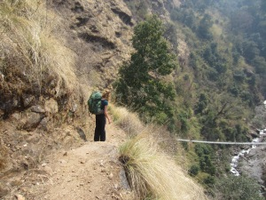 Trail mother watching her boys cross shaky suspension bridge over plunging, rocky river, outside Thulo Syaphru