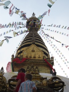 Reaching the top of the eastern staircase with gilded Swayambhunath stupa spire and brass-plated dorje (thunderbolt) symbol (foreground), Swayambhunath