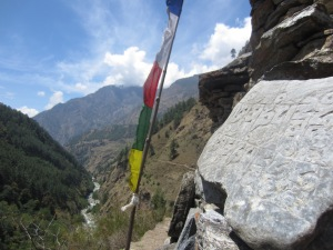 Carved stone on mani wall, prayer flag, and trail far below, reentering the Lower Tsum Valley
