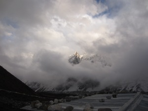 Mountains come out of the sky above the roofs of Larke Phedi on a cold, cloudy afternoon